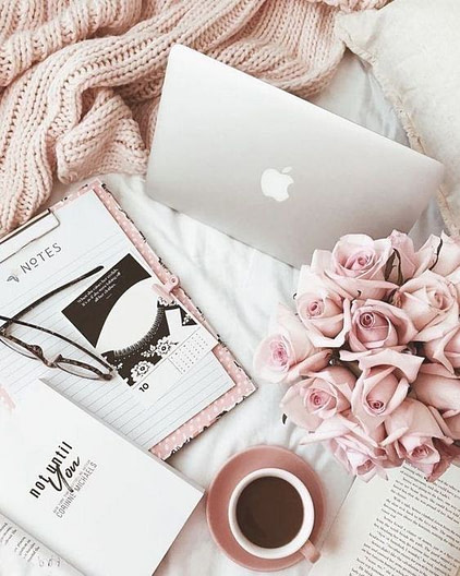 Laptop, notepad, and coffee on a bed with glasses and flowers.
